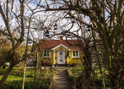 Gul villa fotograferad framifrån. Svensk flagga bredvid dörren.