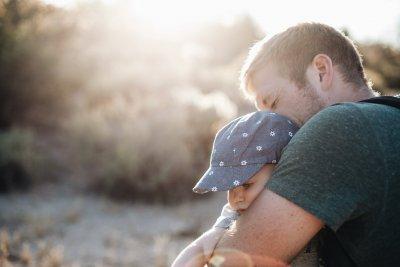 Bilden visar en förälder och litet barn i motljus.