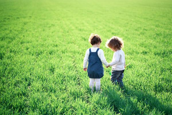 två barn på ett grönt fält
