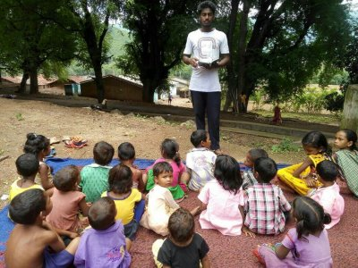 KKC kids listeing to exciting bible stories from the teacher Manasha