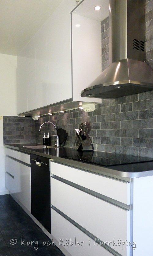 Kök Pinnmogatan, grått kakel och golv mot svart köksbänk.