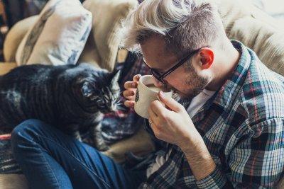 Man i rutig skjorta sitter i soffan bredvid en tabbykatt och dricker en kopp kaffe.