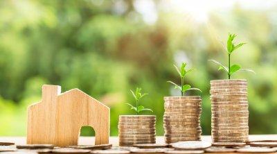 Symbolisk bild av investering i hus med pengar som har små skott