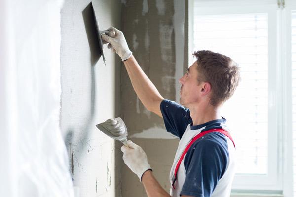 målare spacklar vägg