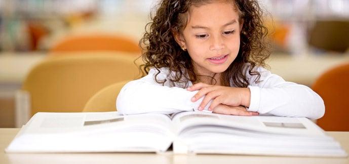 Flicka som läser på biblioteket
