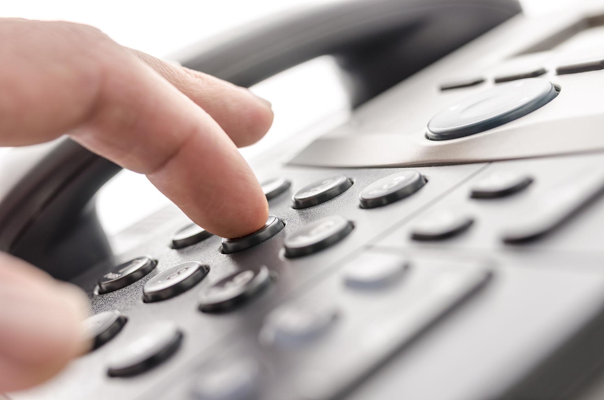 En person slår in ett nummer på en gammal telefon.