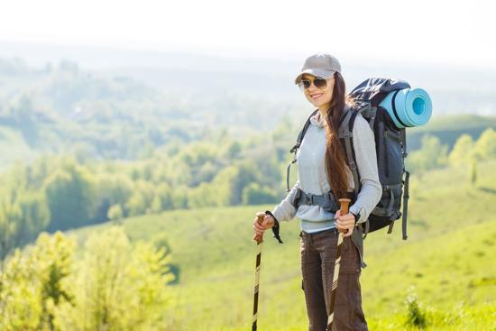 Kvinna i bergen med ryggsäck
