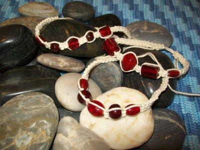 Naturfärgad bomullstråd med glaspärlor i olika former o röda nyanser