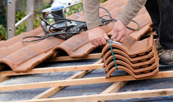 takläggare lägger tegelpannor på takpapp