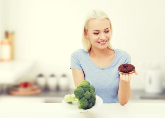 Kvinna väljer mellan munk och broccoli