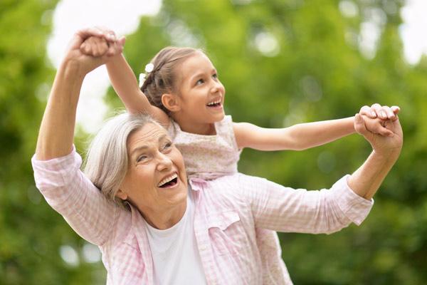 äldre kvinna med åderbråck i ljumsken som leker med sitt barnbarn