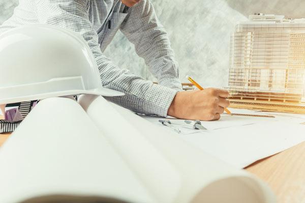 arkitekt tar fram ritning