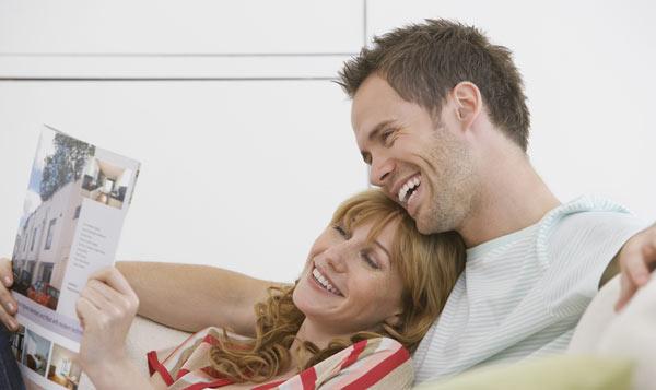ungt par som tittar i katalog med arkitektritade hus
