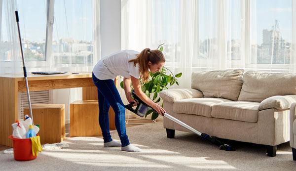 kvinna som städar i sitt vardagsrum