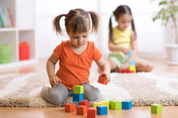Liten flicka leker med färgglada klossar på golv.