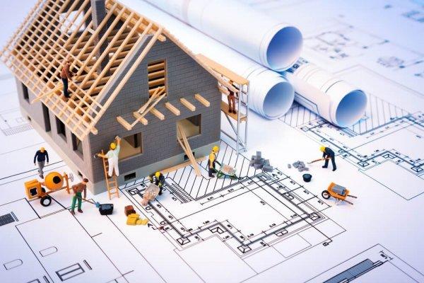 Byggritning med miniatyrhus där leksaksgubbar arbetar