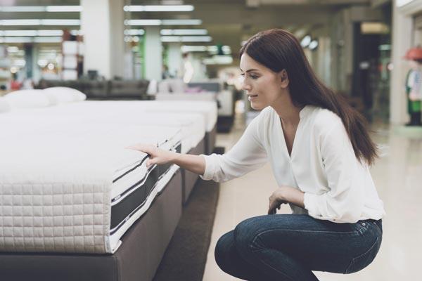kvinna tittar på madrass i butik