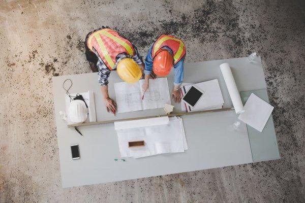 Två män i hjälp står böjda över bord med byggritningar