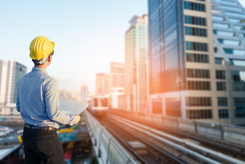 Man i gul hjälm tittar på byggnader