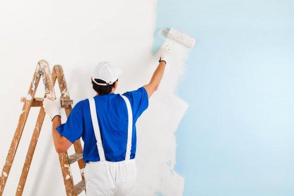 Man målar vägg med vit färg