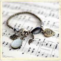 Armband med många berlocker i mässing och pärlemor