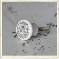 Liten vit porslinsknopp med grått tryck
