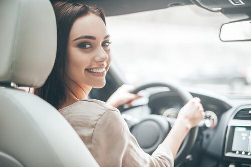Leende kvinna kör bil
