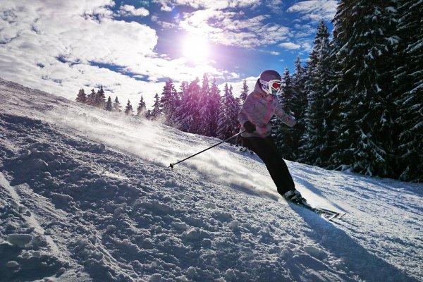 Flicka åker skidor i solsken