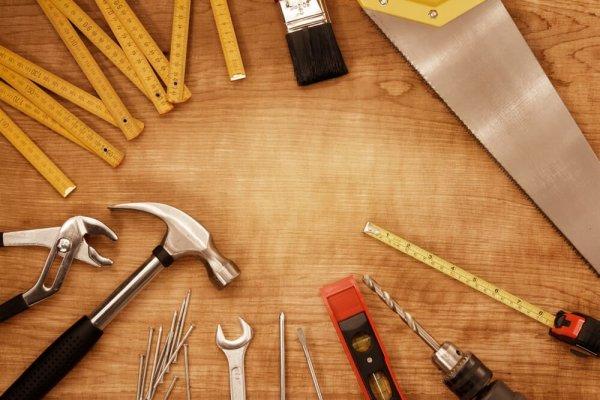 Byggredskap, hammare, såg, skruvmejsel, tumstock mm som ligger på ett bord