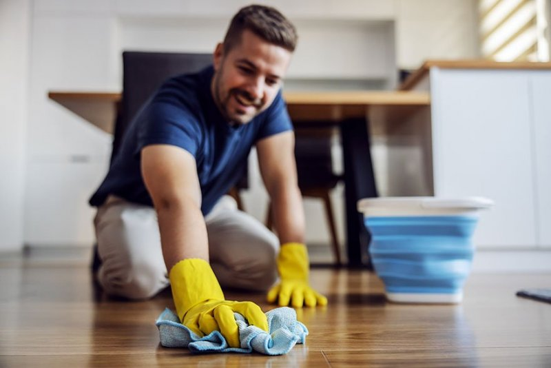 Man utför hemstäd och skrubbar golven.