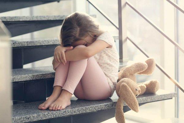 Ledsen flicka sitter i trappa med gosedjur