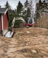 Vi hjälper dig att dränera i Stockholm. Här en grävmaskin som gräver ett dike intill en husgrund.
