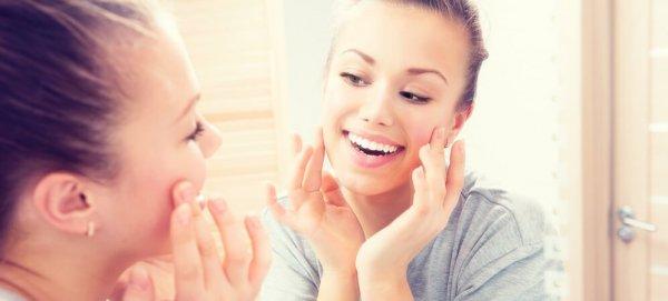 Kvinna nöjd med sina tänder i spegeln