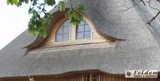 dom z drewna kryty strzechą