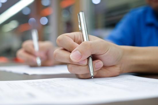 Hand som skriver med penna på papper