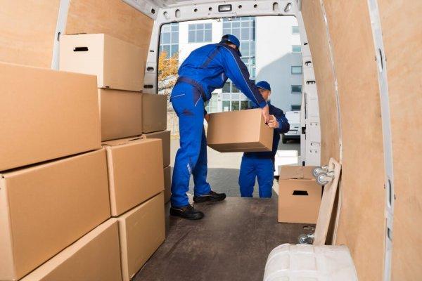 Flyttgubbar lastar på kartonger vid kontorsflytt