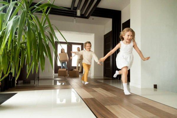 Barn springer in i hus föräldrar står med flyttkartonger