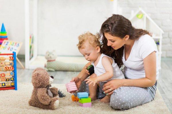 Kvinna leker med litet barn med klossar och nallebjörn