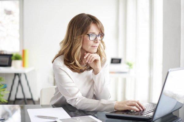 Kvinna sitter framför dator och ser fundersam ut