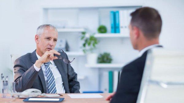 Gråhårig man håller sina glasögon i handen när han pratar med en annan man över ett bord