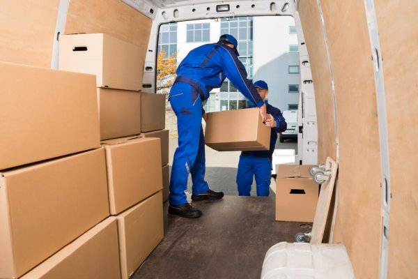 Två flyttgubbar packar kartonger på flyttbil