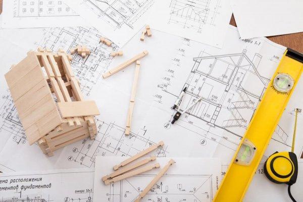Byggritningar och mätverktyg ligger på ett bord