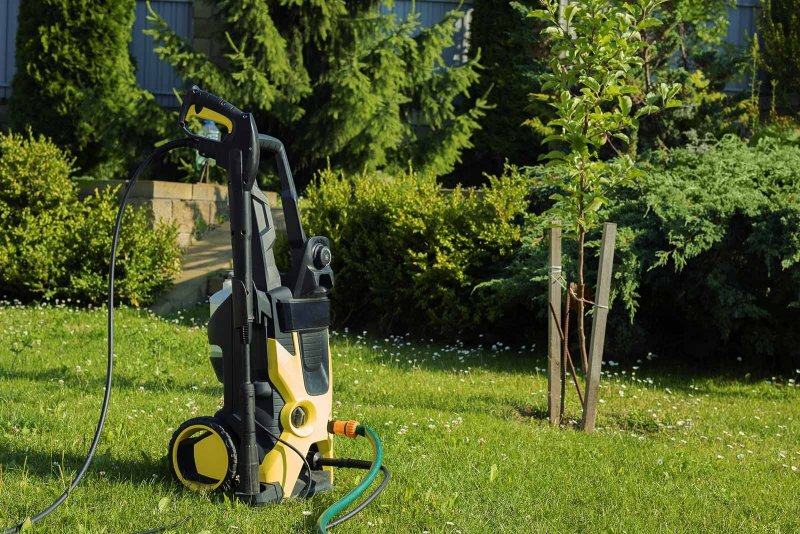 Vi säljer Kärcher högtryckstvätt i Sundsvall och tillhandahåller ett brett sortiment av både begagnat och nytt. Här en högtryckstvätt som står på gräsmattan i en trädgård, en varm och solig dag, redo att göra rent.