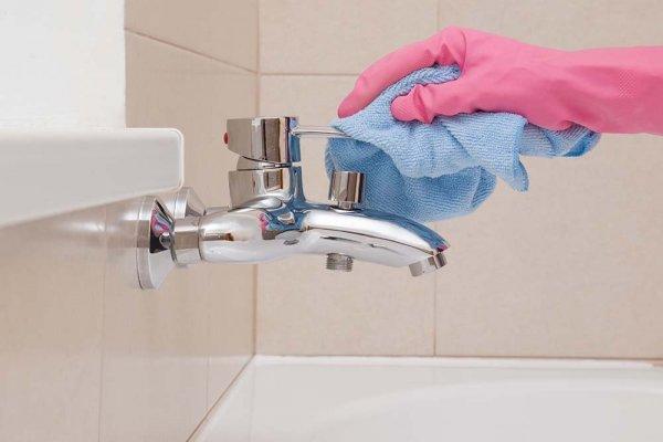 Handskbeklädd hand torkar av kran i badrum