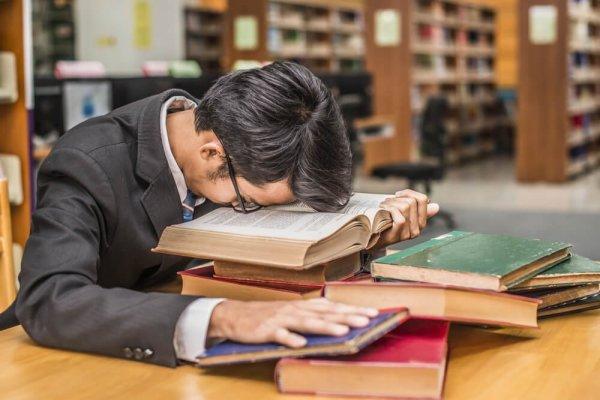 Sovande man över böcker