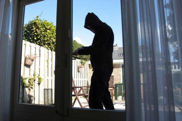 Man i mörka kläder försöker öppna en dörr