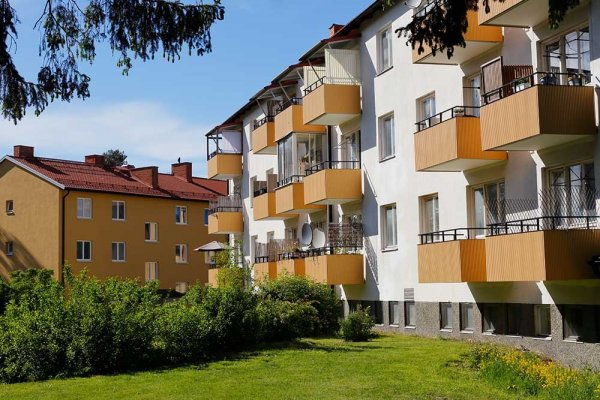 Lägenhetshus med balkonger och gräsmatta och buskar nedanför