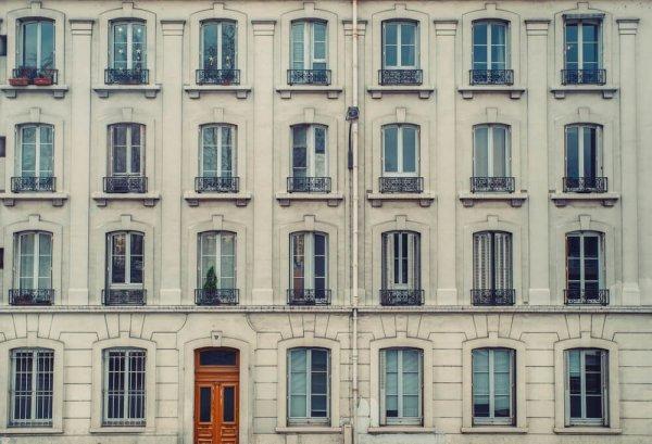 Grå äldre fasad med fina fönster