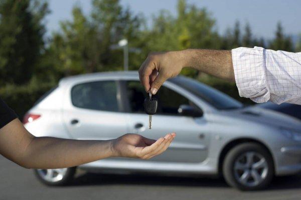Bilhandlare överlämnar bilnyckel till köpare