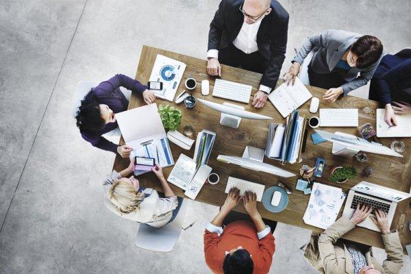 Sju personer sitter runt ett bord med papper, datorer mm